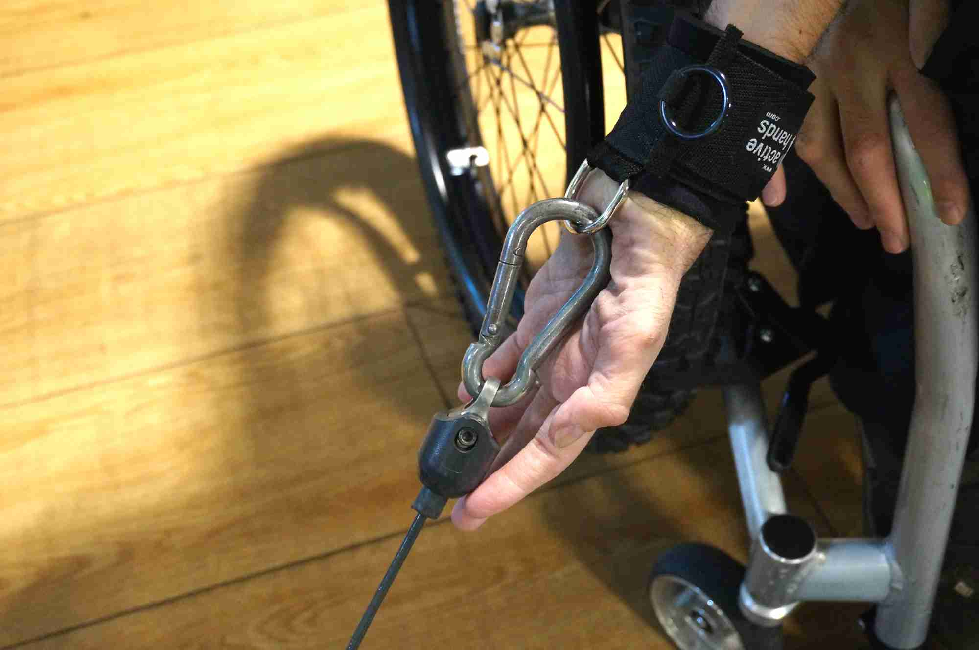 D-ring aid attached to karabiner in gym. Adaptive gym equipment. Suitable for reduced hand function: tetra, quad, cerebral palsy, SCI, spinal cord injury, limb difference, stroke and more.