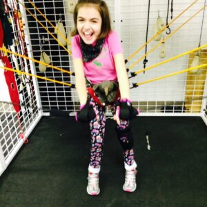 She has Rett syndrome. Here she uses her gripping aids with the bungy cables.