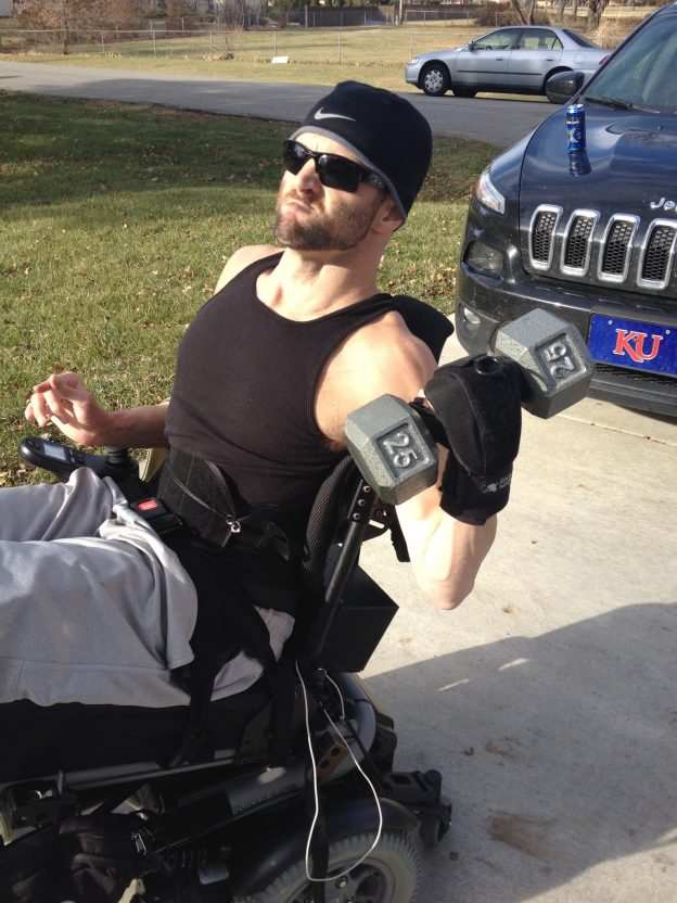 Jerod lifting free weights outside with General Purpose aid. Adaptive gym equipment. Suitable for reduced hand function: tetra, quad, cerebral palsy, SCI, spinal cord injury, limb difference, stroke and more.