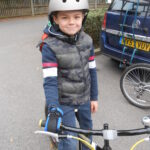 Boy on bike - right hand holding on with Limb difference aid
