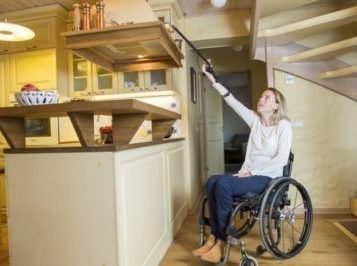 Reacher/ grabber for quadriplegics being used by woman in wheelchair to reach high shelf