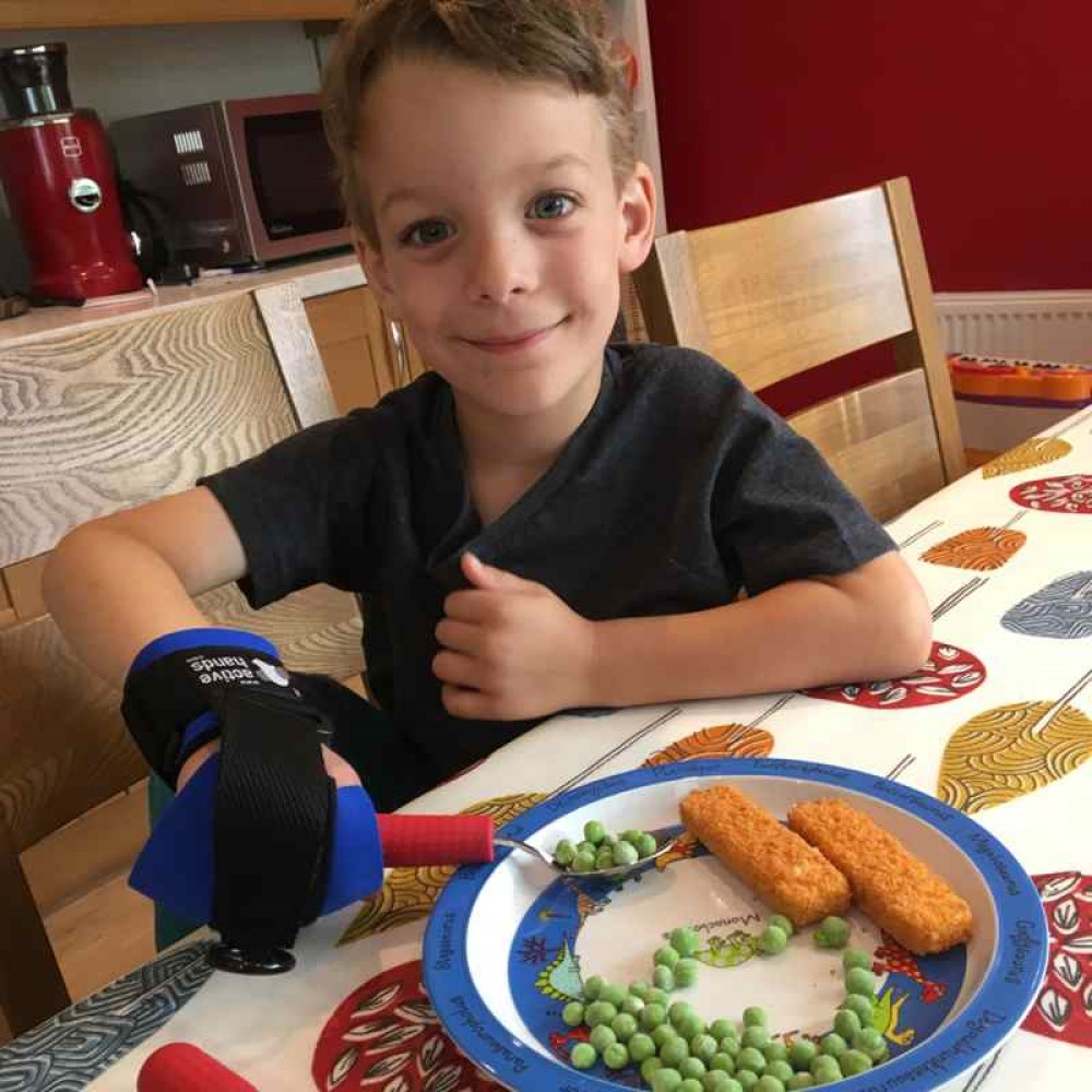 Child holding cutlery grips with mini gripping aid. Suitable for reduced hand function: tetra, quad, cerebral palsy, SCI, spinal cord injury, stroke and more.