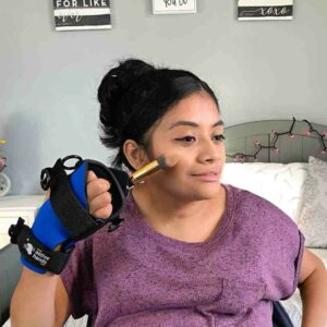 Small Item aid woman putting on make-up. Suitable for reduced hand function: tetra, quad, cerebral palsy, SCI, spinal cord injury, stroke and more.