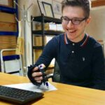 Sam using Small Item gripping aid to write. Suitable for reduced hand function: tetra, quad, cerebral palsy, SCI, spinal cord injury, stroke and more.