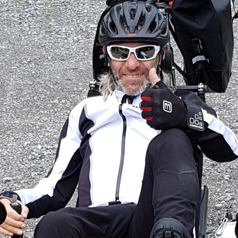 Man gives a thumbs up from his recumbent bike.