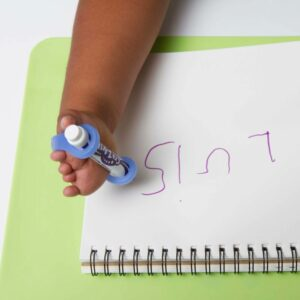 child with limb difference holds pen with easy hold grip