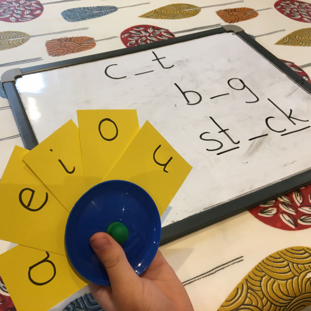 Jake using a card holder to hold letter cards for a spelling activity