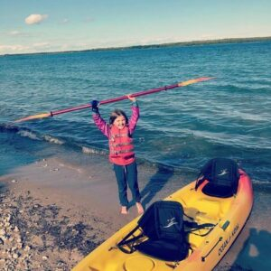 Image shows a child on the shore next to a yellow kayak. She is holding her paddle above her head and grinning. She uses a Limb Difference gripping aid in her right hand.
