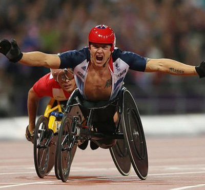 David Weir celebrates his paralympic win, arms outstretched, in his racing wheelchair.