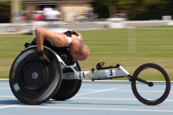 Man races in his racing wheelchair, head down, pushing on his wheels.