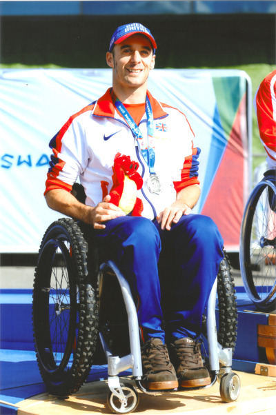 Man in Great Britain sports kit sits in wheelchair smiling, silver medal around his neck.