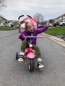 Image shows a girl riding a trike and waving, joyfully. She is gripping the right handlebar with a pink Active Hands mini gripping aid.