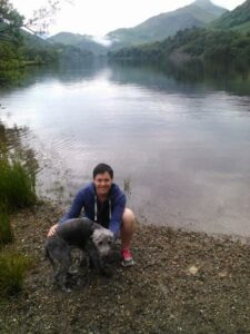 Nat is crouched down by her dog Stan, next to a lake with hilly countryside behind them.