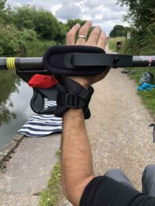picture shows an arm holding a kayak paddle next to a canal, using our kayak adaptations to grip it.
