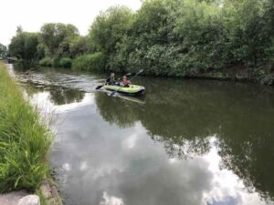 Rob and his son paddle their kayak down the canal.